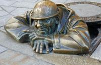 Comical bronze statue in Bratislava, Slovakia.  The debate continues on what the man is doing...